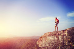 Woman hiker enjoy the view at sunset mountain peak Stock Image