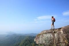 Woman hiker enjoy the view at sunset mountain peak Stock Image
