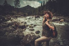Woman hiker enjoying amazing landscapes near wild mountain river. Royalty Free Stock Images