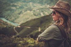Woman hiker enjoying amazing valley landscapes on a top of mountain. Royalty Free Stock Images