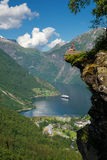 Woman hiker enjoying scenic landscapes at a cliff edge, Geirangerfjord Stock Images