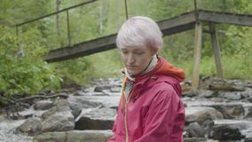Woman hiker in forest outdoor. Tourism concept. Young woman in jacket on the river in the forest stock video footage