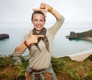 Woman hiker framing with hands in front of ocean view landscape Royalty Free Stock Photography