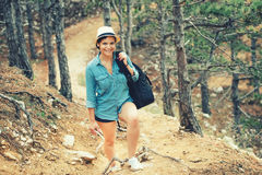 Woman hiker going on path, mountains with backpack. Concept of traveling and trekking on coastline Stock Photography