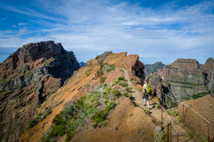 Woman hiker with green backpack is walking to Pico Ruivo hike Royalty Free Stock Photo