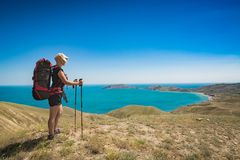 Woman hiker in a hat with backpack and trekking sticks Stock Images