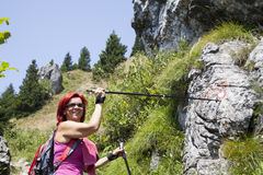 Woman hiker high in the the mountain pointing to the sign post Stock Photos