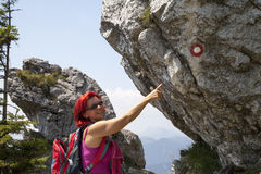 Woman hiker high in the the mountain pointing to the sign post Stock Images