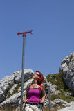 Woman hiker high in the the mountain resting under the sign post Stock Image