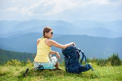 Woman hiker hiking on grassy hill, wearing backpack, using trekking sticks in the mountains. Back view of attractive woman tourist sitting on grassy hill with royalty free stock photo
