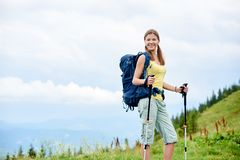 Woman hiker hiking on grassy hill, wearing backpack, using trekking sticks in the mountains stock image