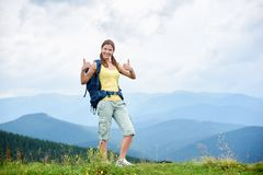 Woman hiker hiking on grassy hill, wearing backpack, using trekking sticks in the mountains. Attractive happy woman hiker hiking in Carpathian mountain trail stock photo