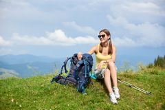 Woman hiker hiking on grassy hill, wearing backpack, using trekking sticks in the mountains. Attractive smiling woman hiker hiking in Carpathian mountain trail stock photos