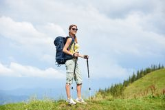 Woman hiker hiking on grassy hill, wearing backpack, using trekking sticks in the mountains. Attractive smiling woman tourist hiking mountain trail, walking on royalty free stock images