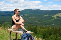 Woman hiker hiking on grassy hill, wearing backpack, using trekking sticks in the mountains. Beautiful happy woman tourist hiking mountain trail, sitting on a stock photo