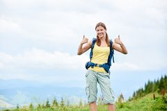 Woman hiker hiking on grassy hill, wearing backpack, using trekking sticks in the mountains. Portrait of attractive smiling woman tourist hiking mountain trail stock photography