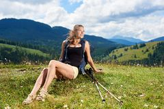 Woman hiker hiking on grassy hill, wearing backpack, using trekking sticks in the mountains. Pretty smiling woman hiker hiking mountain trail, resting on grassy royalty free stock photo