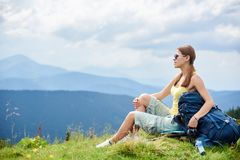 Woman hiker hiking on grassy hill, wearing backpack, using trekking sticks in the mountains. Side view of attractive woman hiker resting on grassy hill with royalty free stock photos