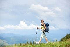 Woman hiker hiking on grassy hill, wearing backpack, using trekking sticks in the mountains. Smiling woman hiker hiking in Carpathian mountain trail, walking on stock photo