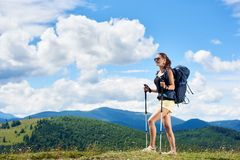 Woman hiker hiking on grassy hill, wearing backpack, using trekking sticks in the mountains. Young woman backpacker hiking mountain trail, walking on grassy hill royalty free stock photo