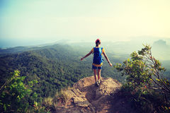 Woman hiker hiking on mountain peak. Successful woman hiker hiking on mountain peak royalty free stock photos