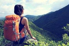 Woman hiker hiking on mountain peak. Successful young woman hiker hiking on mountain peak Royalty Free Stock Image