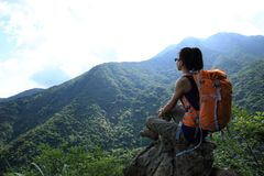 Woman hiker hiking on mountain peak. Successful young woman hiker hiking on mountain peak Stock Photography