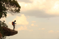 Woman hiker hiking on mountain top cliff. Young woman hiker hiking on mountain top cliff stock photos