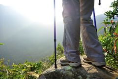 Woman hiker hiking stand on cliff. Woman hiker legs hiking stand on cliff stock photo