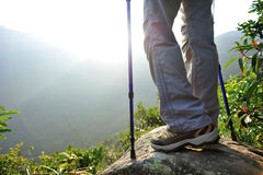 Woman hiker hiking stand on cliff. Woman hiker legs hiking stand on cliff stock photography
