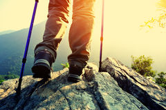 Woman hiker hiking stand on cliff. Woman hiker legs hiking stand on cliff royalty free stock photography