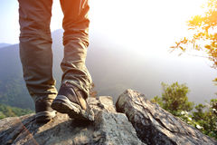 Woman hiker hiking stand on cliff. Woman hiker legs hiking stand on cliff royalty free stock images