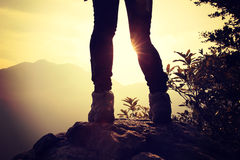 Woman hiker hiking stand on cliff. Woman hiker legs hiking stand on cliff stock images