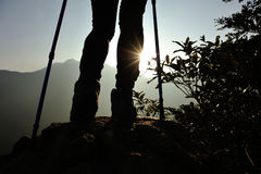Woman hiker hiking stand on cliff. Woman hiker legs hiking stand on cliff royalty free stock photo