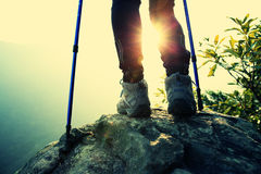 Woman hiker hiking stand on cliff. Woman hiker legs hiking stand on cliff royalty free stock image