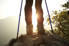 Woman hiker hiking stand on cliff. Woman hiker legs hiking stand on cliff Royalty Free Stock Photos