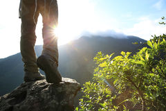 Woman hiker hiking stand on cliff. Woman hiker legs hiking stand on cliff stock photos