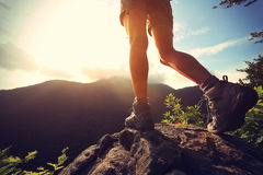 Woman hiker hiking stand on cliff. Woman hiker legs hiking stand on cliff stock image