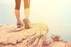 Woman hiker hiking stand on seaside rock Royalty Free Stock Photography