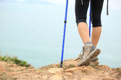 Woman hiker hiking stand on seaside rock. Woman hiker legs hiking stand on seaside rock royalty free stock images