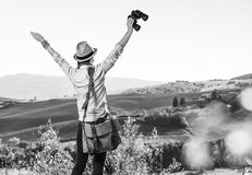 Woman hiker hiking in Tuscany with binoculars rejoicing. Discovering magical views of Tuscany. Seen from behind woman hiker with bag hiking in Tuscany with Royalty Free Stock Photos