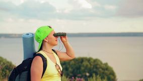 Woman hiker on a hill with a backpack behind her, looking through binoculars at nature. Shooting from the side stock video