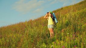 Woman hiker on a hill with a backpack behind her, looking through binoculars. Overall plan stock footage
