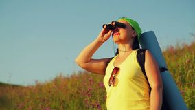 Woman hiker on a hill with a backpack behind her, looking through binoculars at the sights. The average plan stock video footage