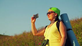 Woman hiker on a hill with a backpack over his shoulders and binoculars takes a selfie. The average plan stock footage