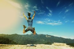 Woman hiker jumping on mountain top. Successful woman hiker jumping on mountain top Royalty Free Stock Image