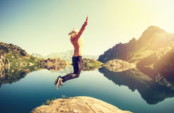 Woman hiker jumping up Flying levitation with lake and mountains on background Royalty Free Stock Photo