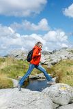 Woman hiker jumps over stones Stock Photo