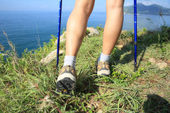 Woman hiker legs hiking on seaside mountain Stock Images