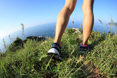 Woman hiker legs hiking on seaside mountain Stock Photo